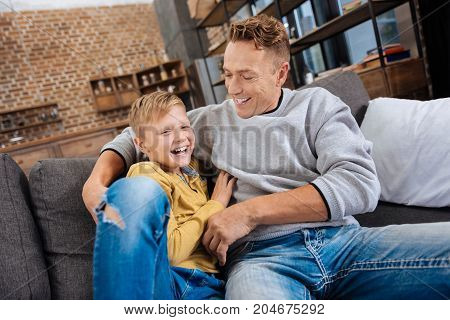 Precious family moments. Charming young man sitting on the couch with his pre-teen son, cuddling him and tickling while happily laughing together with him
