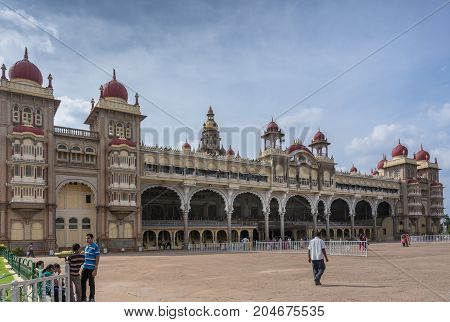 Mysore India - October 27 2013: Wide shot of East facade of Mysore Palace under cloudscape. Beige building with towers and maroon domes. Seen from Southeast corner.