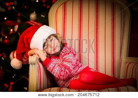Beautiful child dressed in Santa Claus hat. Funny baby sleeping against Christmas tree. Xmas holiday concept