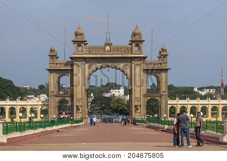 Mysore India - October 27 2013: Closeup of brown stone main East Gate to Mysore Palace under blue sky. Yellow wing corridor on both sides. Visitors and city view with trees.