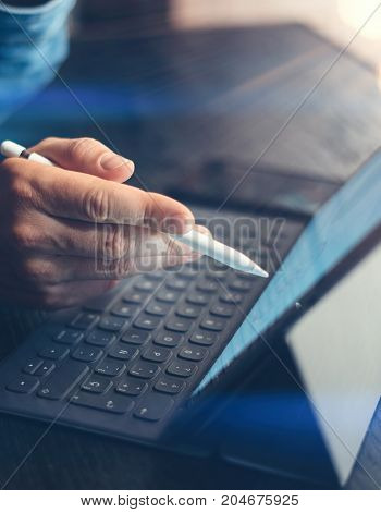 Businessman using electronic tablet keyboard-dock station at office. Closeup male hand pointing on device screen electronic pen. Vertical.Cropped.Flares effect