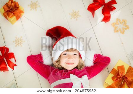 Happy child with Christmas gift. Funny baby dressed in Santa Claus hat. Kid playing at home. Xmas holiday concept