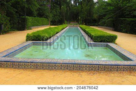 a magnificent foutain garden of la cruz ( seville spain )
