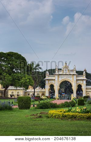Mysore India - October 27 2013: Green garden with flowers in front of closed North Gate to Mysore Palace under cloudscape.