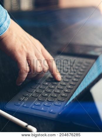 Man working at office. Closeup view of male finger touching electronic tablet keyboard-dock station. Vertical, sunlight effect