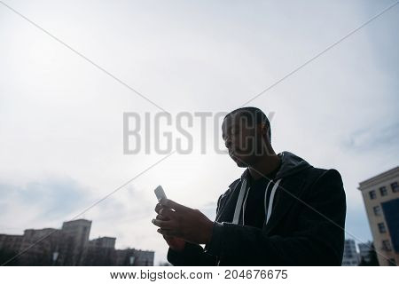 Social media communication outdoors. Black male typing with smartphone. Sky background with free space, modern technology, street style