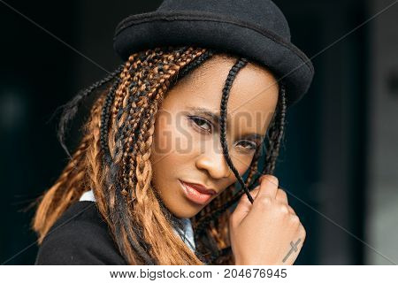 Seductive young African American female. Pretty fashion black woman in selective focus, shy lady on dark background, stylish haircut, seduction concept