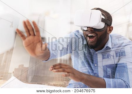 Unreal emotions. Close up of young African American wearing virtual glasses while putting his palm forward and expressing surprise