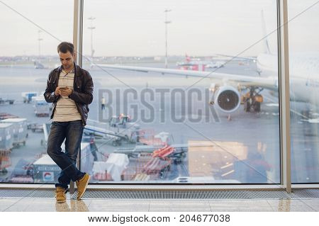Businessman talking on the phone at airport terminal.