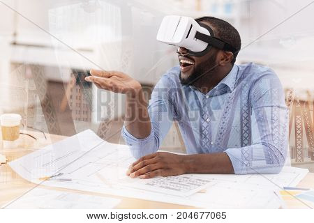 Cannot believe it. Positive pleasant African American wearing virtual mask while sitting at the table and expressing delightful emotions