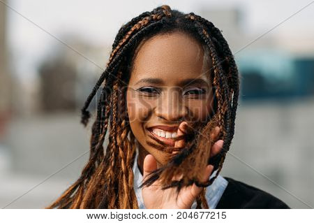 Merry black female have fun outdoors. Stylish model smile. Joyful smiling woman in selective focus, fashion style, happiness concept