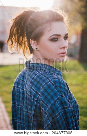 Stylish hipster girl. Thoughtful lady. Female fashion portrait in focus on foreground, urban life, atmospheric backlight, beauty concept