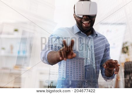 Look at me. Smiling young man wearing virtual glasses while standing in front of you and pointing two fingers