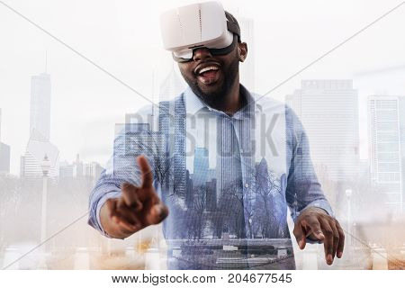 Great excitement. Young cheerful African American wearing virtual device on his head while looking at his fingers