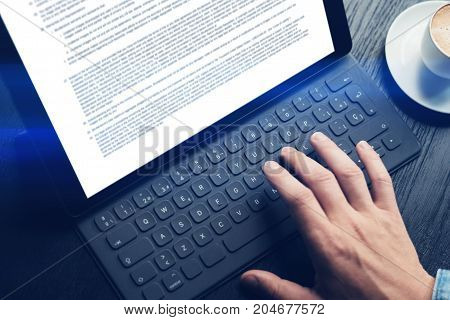 Closeup view of male hands typing on electronic tablet keyboard-dock station. Text information on device screen. Man working at office.Horizontal
