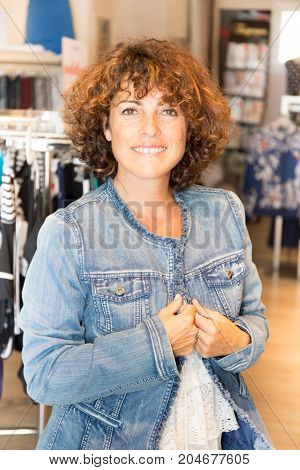 Young Girl In Shop Buying Clothes And Try Jeans Jacket