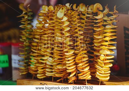 Golden Potato Chips On A Thin Wooden Stick. Close Up. Food Background