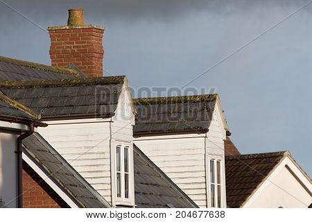 Dormer roof windows. Loft structures on modern town house buildings. White cladding and slate tiles on dormer windows.