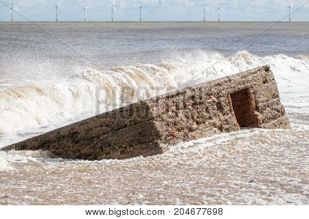 Rising sea level. Wave flooding beach and engulfing historical concrete WW2 military defense structure.