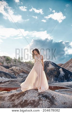 Girl In A Light Blue Dress Standing In The Wind With Mountains In The Background. Clean And Immacula