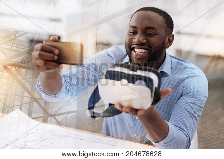 Will remember. Close up of optimistic young man keeping virtual glasses in hand and making selfie while being excited