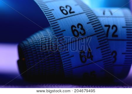 Measure Tape In Deep Blue Color On Blue Background, Defocused.