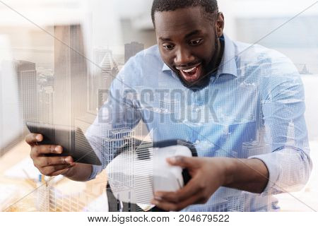 Amazing technology. Close up of happy young man looking surprised while keeping device and virtual reality tool in hands