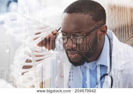 Concentration on working. Close up of young attentive doctor with glasses making a research while being attentive