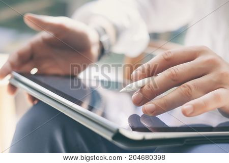 Closeup view of coworker holding digital tablet on hand and using electronic pen while working at office.Pointing tablet screen.Blurred background.Horizontal