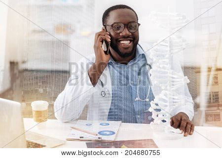 Nice conversation. Close up of pleased smiling doctor sitting in the office while having a talk on the mobile phone