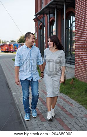 family couple men and a young pregnant woman walking holding hands and laughing along the city windows