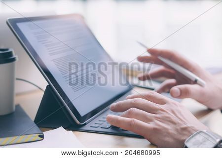 Blogger working at studio.Closeup view of male hands typing on electronic tablet keyboard-dock station.Business text information on device screen. Horizontal.Blurred background