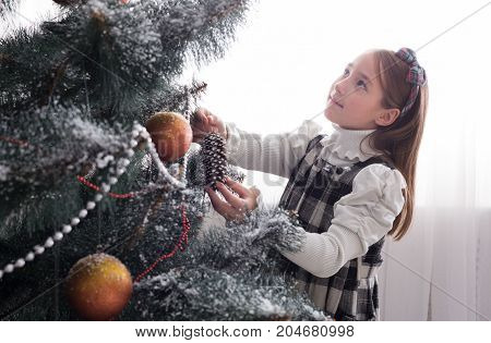 Pretty little girl decorate big christmas tree. Child prepare to winter holiday, hang decorations, tinsel, bead garland, ornaments, baubles and balls. Christmas atmosphere at cosy home