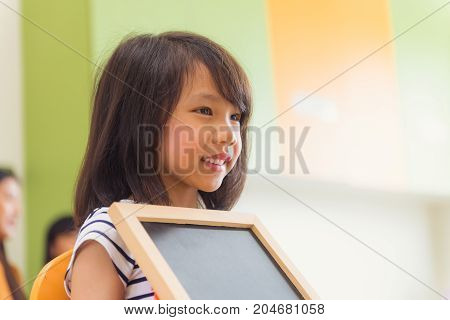 Cute asian girl holding blank blackboard with happy face in kindergarten classroom kindergarten education concept Vintage effect style pictures.
