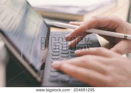 Closeup view of male hands typing electronic tablet keyboard-dock station.Blogger using mobile touchpad for work.Horizontal, blurred background.Cropped