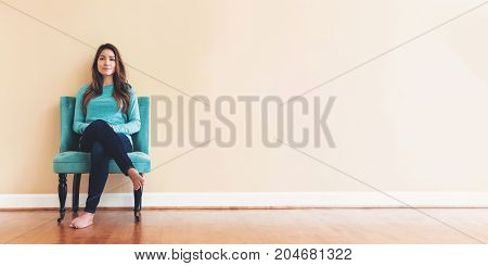 Young latina woman sitting in a chair in a large interior room