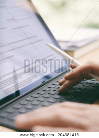 Blogger using mobile touchpad for work.Closeup view of male hands typing electronic tablet keyboard-dock station.Vertical, blurred background