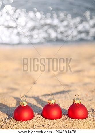 Three Red Christmas Balls On Sea Coast