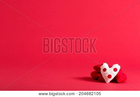 Handmade heart cushions on a red background
