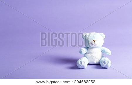Baby blue child's teddy bear stuffed animal on a purple background