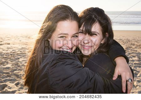 Mature Mother Hugging With Her Teen Daughter Outdoor In Nature On Sunny Day Beach