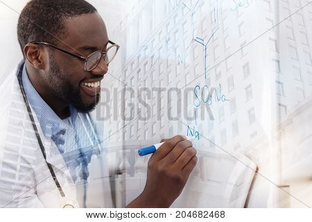 Creating new formula. Close up of smiling African American doctor writing down chemical composition while using a board and marker pen