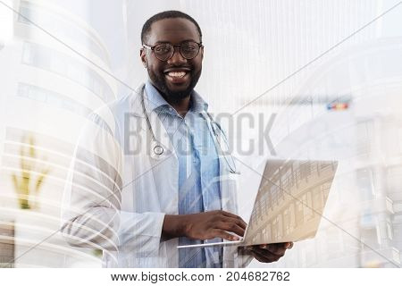 Making a research. Successful African American doctor holding a laptop in hands while looking at you and being in a perfect mood