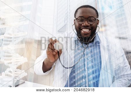 Caring about health. Close up amused African American doctor using earphones while pointing at you and smiling