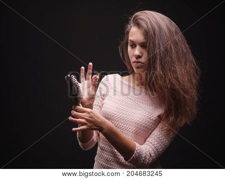 Upset, stressed, sick young female pulling tangled hair on the black background. Concerned woman holding a hair brush for hair touching her brown hair. Stress and depression symptoms and treatment.