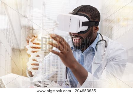 Fantastic work. Close up of smiling African American researcher touching genome model while looking at it through virtual glasses