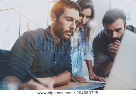 Teamwork concept.Young coworkers working with new business project in modern office.Group of three people analyze data on laptop computer.Horizontal.Blurred background.Flares