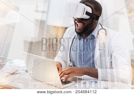 Much fun. Amused successful researcher wearing virtual glasses while working with a laptop and expressing cheer