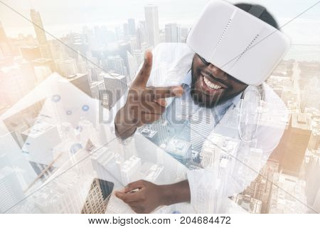 Exciting emotions. Young pleased African American doctor putting forward two fingers while looking at them through virtual glasses and smiling