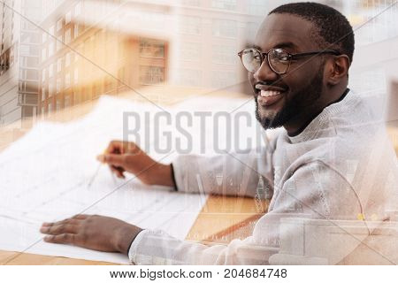 Busy day. Close up of smiling hardworking man with glasses sitting at the table while looking at you and expressing positive emotions